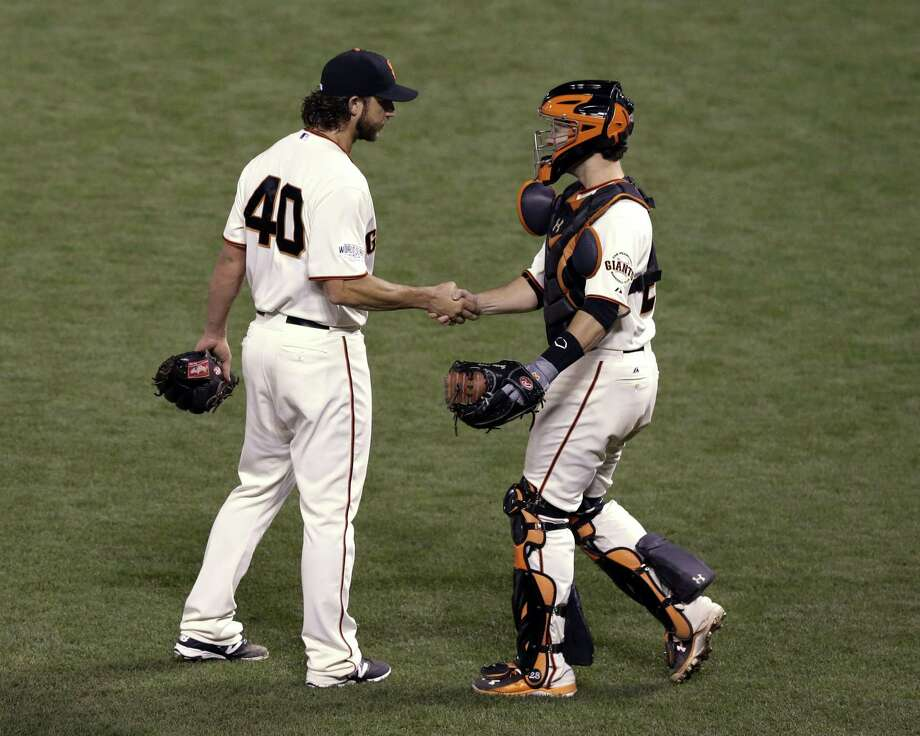 San Francisco Giants catcher Buster Posey shakes hands with pitcher Madison Bumgarner after defeating the Kansas City Royals 5-0 in Game 5 of baseball's World Series Sunday, Oct. 26, 2014, in San Francisco. The Giants lead 3-2 in the series. (AP Photo/Jeff Chiu) Photo: AP / AP
