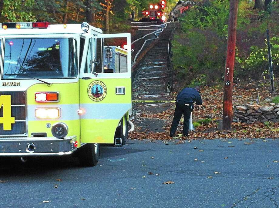 A North Haven police officer tapes off the entrance to 22 Helen Drive. A 28-year-old man was found dead after a fire broke out early Monday. Photo: Wes Duplantier — New Haven Register