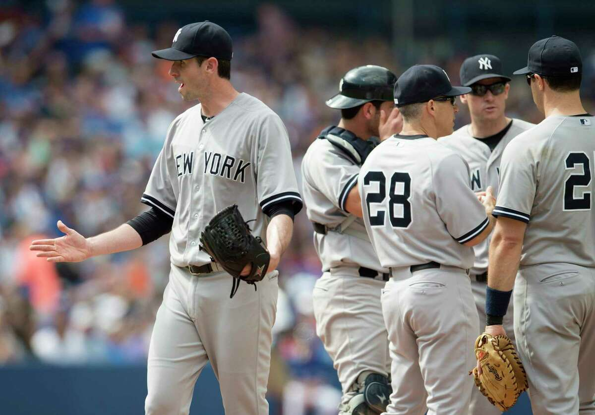 New York Yankees starting pitcher Brandon McCarthy, left, gestures toward home plate umpire Chad Fairchild after being pulled in the seventh inning Sunday.
