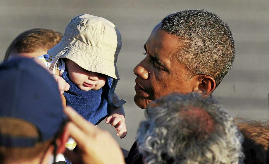 President Obama holds up four-month-old Ryan Kelley, of Richmond, R.I., while greeting a gathering shortly after arriving at T.F. Green Airport in Warwick, R.I. on Aug. 29, 2014. The president traveled to Rhode Island to attend a Democratic fundraiser in Newport on Friday. Photo: AP Photo/Charles Krupa   / AP