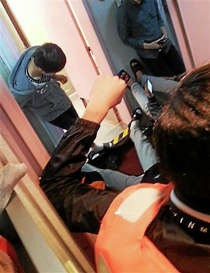 In this April 16, 2014 photo taken from the mobile phone of deceased South Korean high school student Park Su-hyeon and released by his father Park Jong-dae, students are shown inside the sinking ferry Sewol on waters near Jindo, South Korea. Soon after the ferry begins to tilt, nervous laughter can be heard from the high school students huddled below deck. In video clips from the cellphone of Park Su-hyeon, a victim of the disaster that has shaken South Korea, the teenagers talk of taking selfies, wonder if they'll make the news and discuss posting about the excitement later on Facebook. (AP Photo/Park Su-hyeon courtesy of the Park Family) Photo: ASSOCIATED PRESS