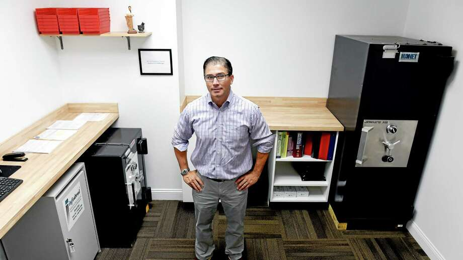 (Arnold Gold-New Haven Register)  Nick Tamborrino, manager of the medical marijuana dispensary, Bluepoint Wellness of Connecticut, is photographed in the Branford facility on 8/29/2014.  The two safes are for storing different types of marijuana. Photo: Journal Register Co.