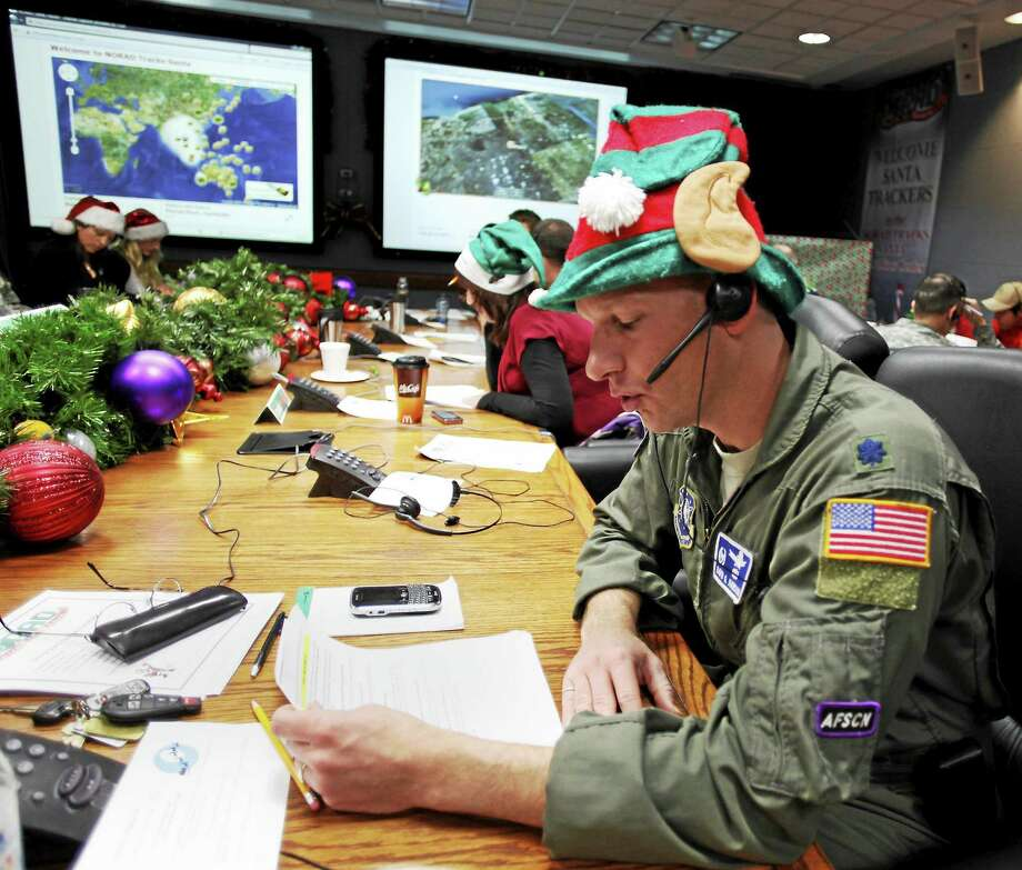 In this Dec. 24, 2010, file photo, Air Force Lt. Col. David Hanson of Chicago takes a phone call from a child in Florida at the Santa Tracking Operations Center at Peterson Air Force Base near Colorado Springs, Colo. (AP Photo/Ed Andrieski) Photo: AP / AP2010