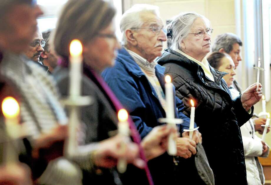 (Photo by Peter Hvizdak-New Haven Register)  People hold a candlelight vigil Saturday for the dead and injured protesters in the Ukraine during the 9th Ukrainian-Americans of Connecticut Community Meeting March 1, 2014 at the St. Michael's Ukrainian Catholic Church Hall in New Haven before a discussion on the unrest in the ukraine and U.S. - Ukrainian relations. Photo: New Haven Register / ©Peter Hvizdak /  New Haven Register