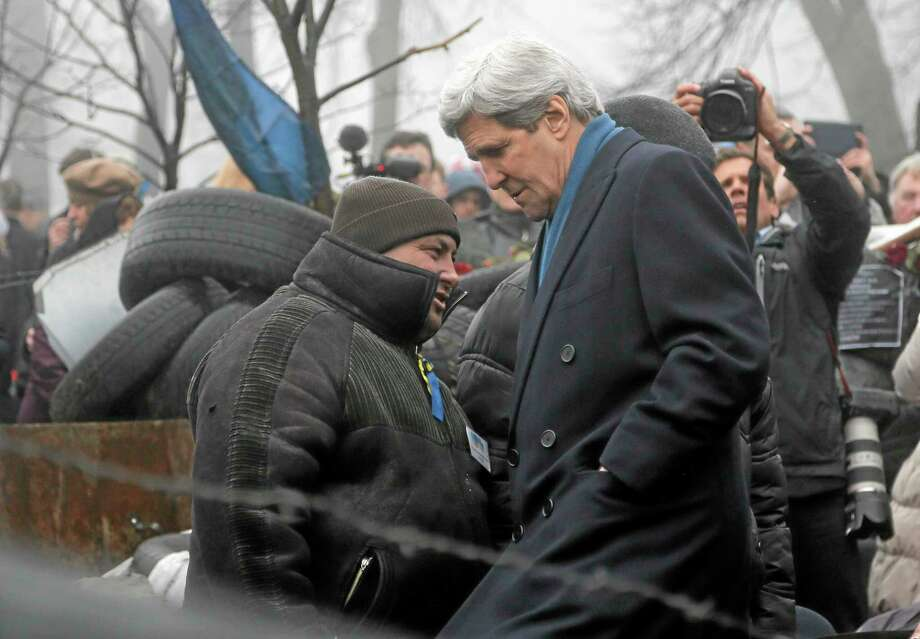 U.S. Secretary of State John Kerry, right, inspects protesters barricades in Kiev, Ukraine, Tuesday, March, 4, 2014. In a somber show of U.S. support for Ukraineís new leadership, Secretary of State John Kerry walked the streets Tuesday where nearly 100 anti-government protesters were gunned down by police last month, and promised beseeching crowds that American aid is on the way.  The Obama administration announced a $1 billion energy subsidy package in Washington as Kerry was arriving in Kiev.(AP Photo/Efrem Lukatsky) Photo: AP / AP