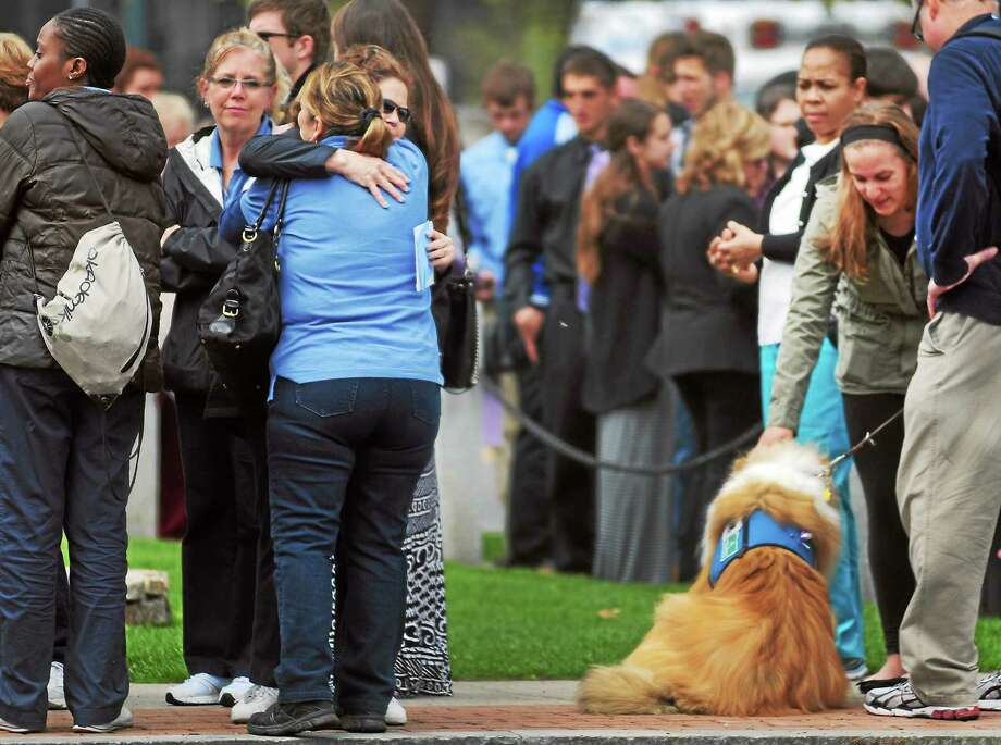 Two women hug, left, and a therapy dog does his job, right, as  people wait in at the Cody-White Funeral Home on North Broad Street in Milford Thursday during the wake for Maren Sanchez. Photo: Peter Hvizdak — New Haven Register    / ©Peter Hvizdak /  New Haven Register