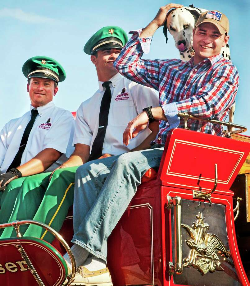 Peter Pacanski, right, an Army veteran who served in Iraq and Afghanistan, wanted his picture taken not with the famed Budweiser Clydesdales, but with Brewer, the Budweiser Dalmation. Brewer obliged and moved in for the shot. Looking on are drivers Dave Thomas, left, and Eric Soto. Photo: Melanie Stengel — New Haven Register