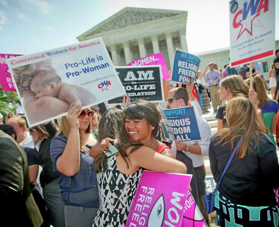 Demonstrators embrace as they react to hearing the Supreme Court's decision on the Hobby Lobby case outside the Supreme Court in Washington, Monday, June 30, 2014. The Supreme Court says corporations can hold religious objections that allow them to opt out of the new health law requirement that they cover contraceptives for women. Photo: (AP Photo/Pablo Martinez Monsivais) / AP