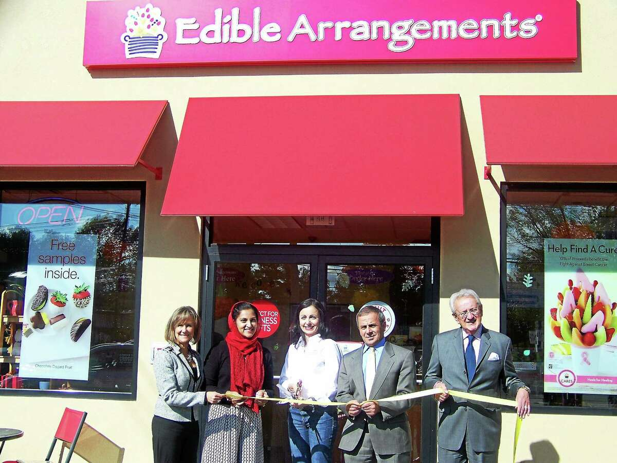 CONTRIBUTED PHOTO - BRITTANY BISHOP From left, Dee Prior Nesti, executive director of the Quinnipiac Chamber of Commerce; Asma Farid, owner of Edible Arrangements International LLC; Allie Fraschilla, owner of Edible Arrangements of North Haven; Mike Freda, first selectman of North Haven; Tony Rescigno, president of the Greater New Haven Chamber of Commerce and the Quinnipiac Chamber of Commerce, celebrate the ribbon-cutting at Edible Arrangements of North Haven, 101 Washington Ave., recently. In addition to their abundance of fruit bouquets, the shop offers a selection of delicious and nutritious smoothies, fruit parfaits and fruit sundaes. The location is open Monday through Friday from 8 a.m. to 7 p.m., Saturday from 8 a.m. to 5 p.m. and Sunday from 10 a.m. to 3 p.m.