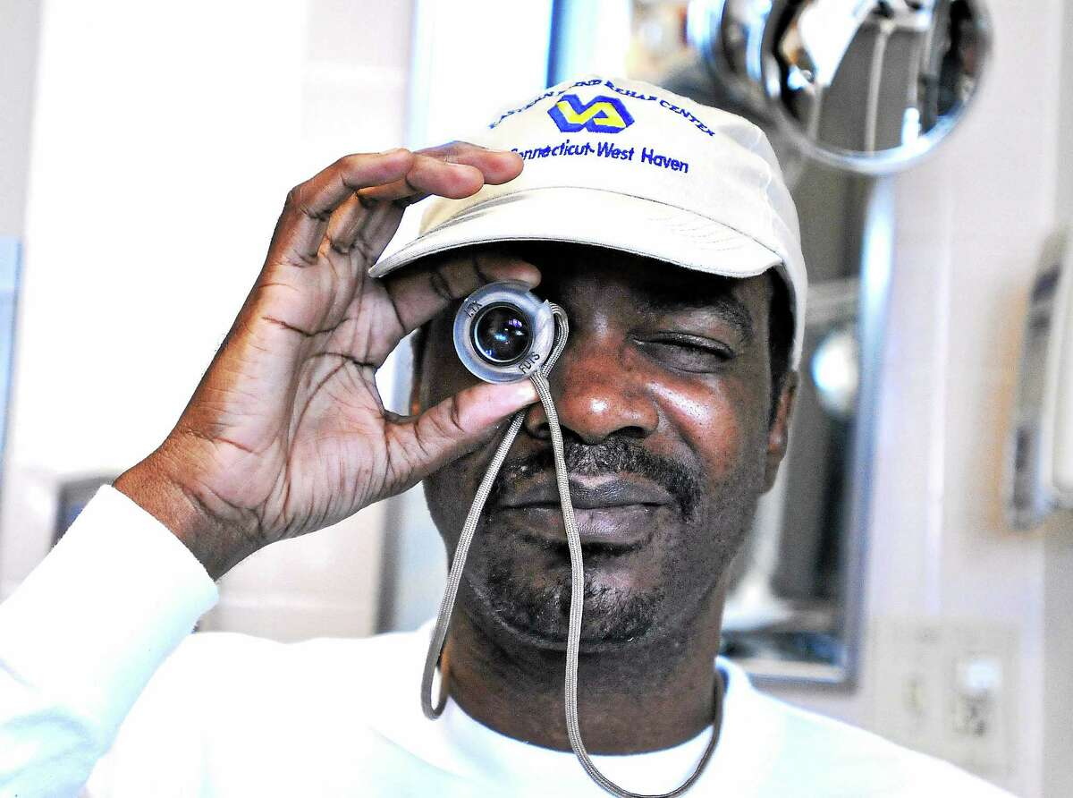 Kenneth Holmes, an army veteran from Philadelphia, uses a high-powered monocle as he works with low-vision specialist Chris Newton at the Eastern Blind Rehabilitation Center last week.