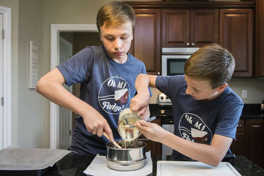 Marshall McGaugh, 14, and Michael McGaugh, 12, make a batch of fudge to sell at the Midland Farmers Market at their home on June 9. The brothers participated in the Young Entrepreneurs Academy to create their business, Oh MI Fudge. Photo: (Danielle McGrew Tenbusch/for The Daily News)