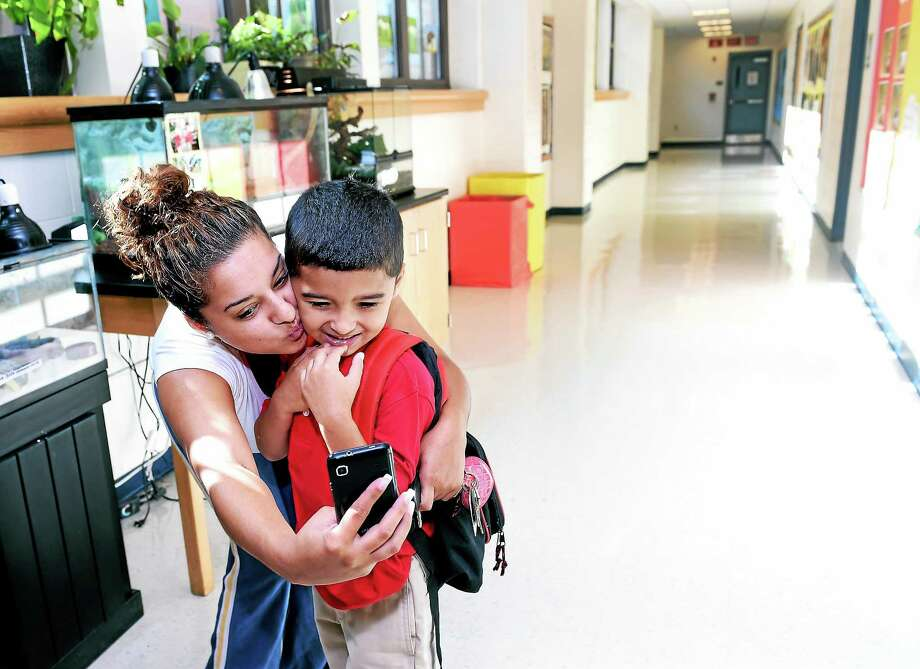 Keila Vasquez takes a photograph with her first-grader son Wilson, 5, on the first day of school at Mauro-Sheridan Interdistrict Magnet School for Science, Technology & Communications in New Haven Thursday. Photo: Arnold Gold — New Haven Register