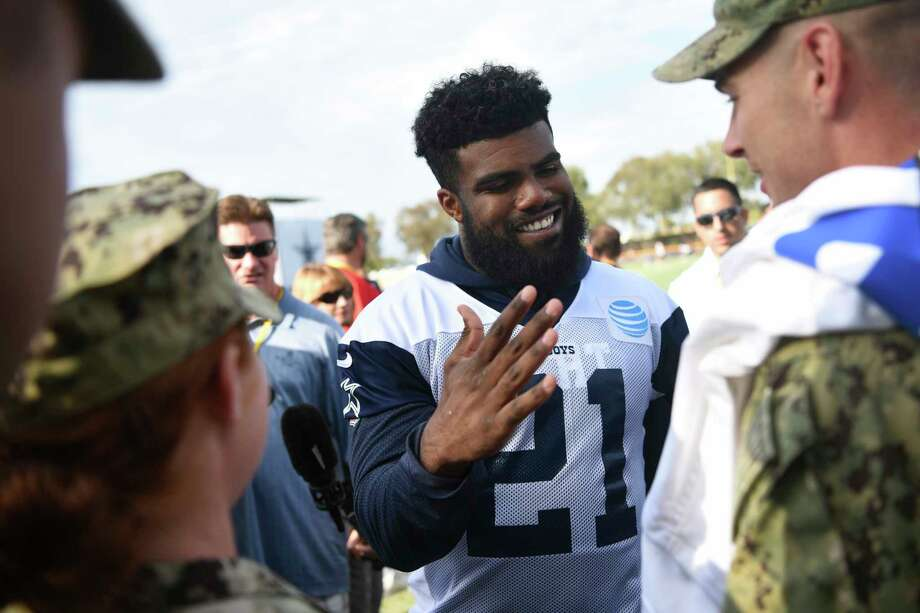Dallas Cowboys running back Ezekiel Elliott (21) greets Navy personnel from Naval Base Ventura County following practice at the NFL football team's training camp in Oxnard, Calif., Monday, July 24, 2017. (AP Photo/Michael Owen Baker) Photo: Michael Owen Baker, Associated Press / FR171390 AP