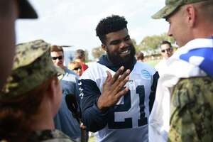 Dallas Cowboys running back Ezekiel Elliott (21) greets Navy personnel from Naval Base Ventura County following practice at the NFL football team's training camp in Oxnard, Calif., Monday, July 24, 2017. (AP Photo/Michael Owen Baker)