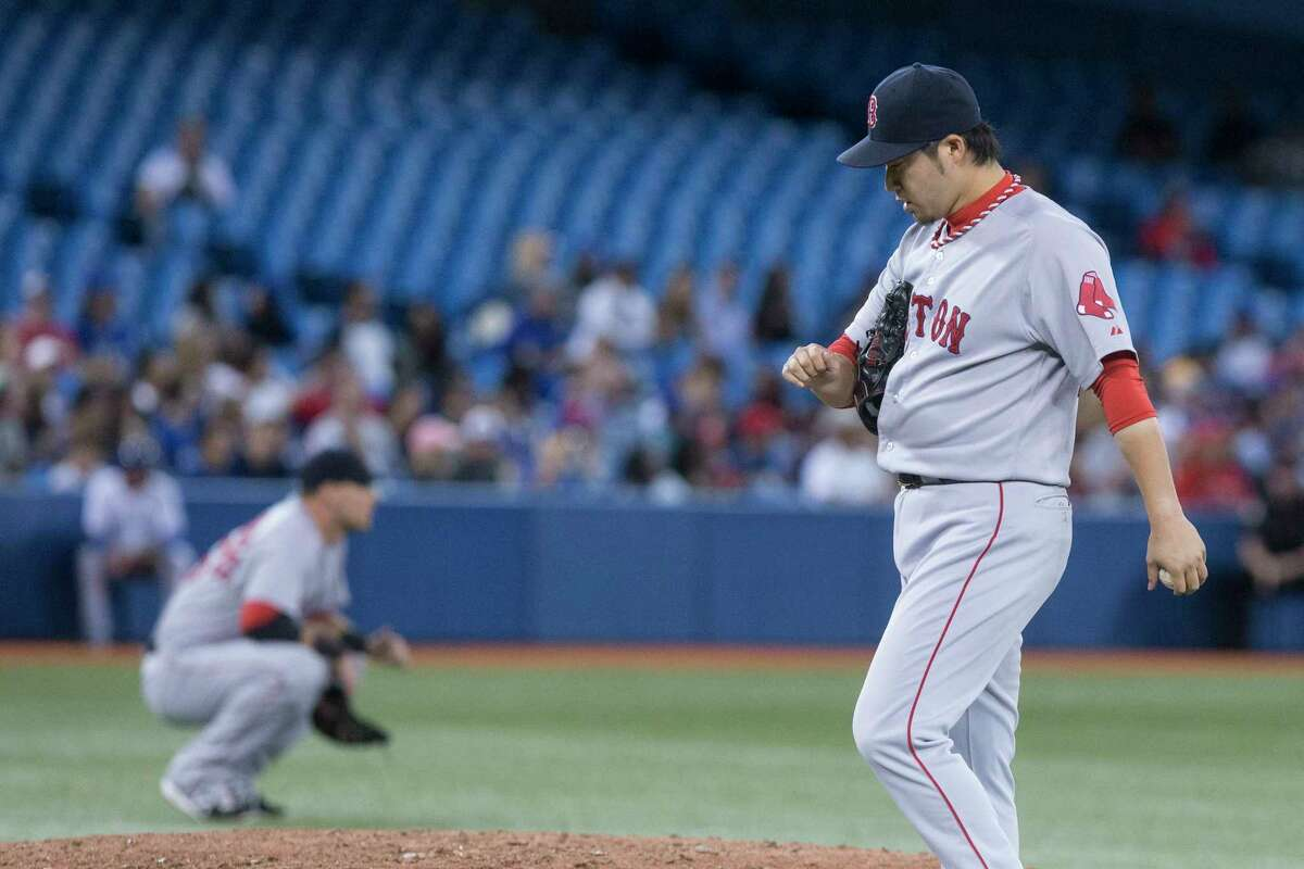 Red Sox pitcher Junichi Tazawa reacts after Toronto Blue Jays' Kevin Pillar hits a double during a four-run seventh inning in the Blue Jays' 5-2 win.