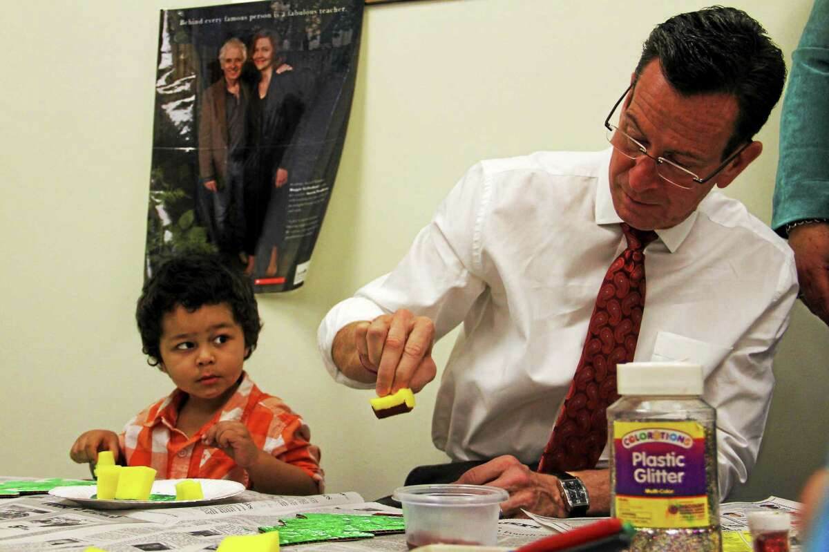 Marcelo Ferreira, 3, watches Gov. Dannel Malloy paint a Christmas tree on Friday, Dec. 19, at the Torrington Child Care Center. Malloy stopped by along with a Congressional delegation to promote $12.5 in federal funding to help expand preschool services, including the Child Care Center, in the state. Esteban L. Hernandez Register Citizen