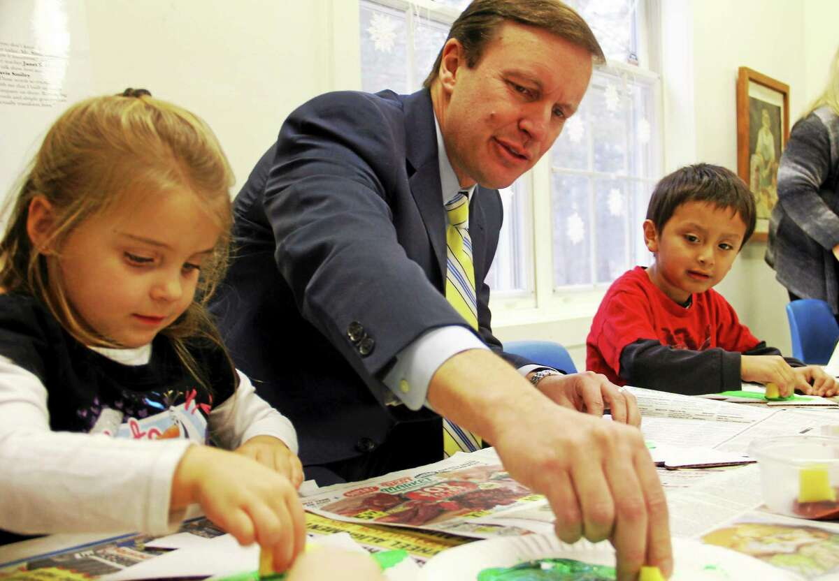 Sen. Chris Murphy paints a Christmas tree between Hannah Baker, 4, and Jack Zhumo, 4, on Friday, Dec. 19, at the Torrington Child Care Center. Esteban L. Hernandez Register Citizen