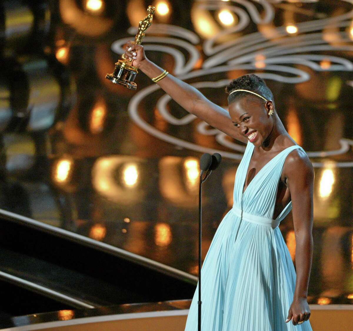 """Lupita Nyongío accepts the award for best actress in a supporting role for """"12 Years a Slave"""" during the Oscars at the Dolby Theatre on Sunday, March 2, 2014, in Los Angeles. (Photo by John Shearer/Invision/AP)"""