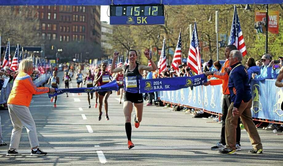 Molly Huddle breaks the tape to win the women's division in the 5-kilometer run on April 19 in advance of the Boston Marathon. Photo: Elise Amendola — The Associated Press File Photo   / AP2014