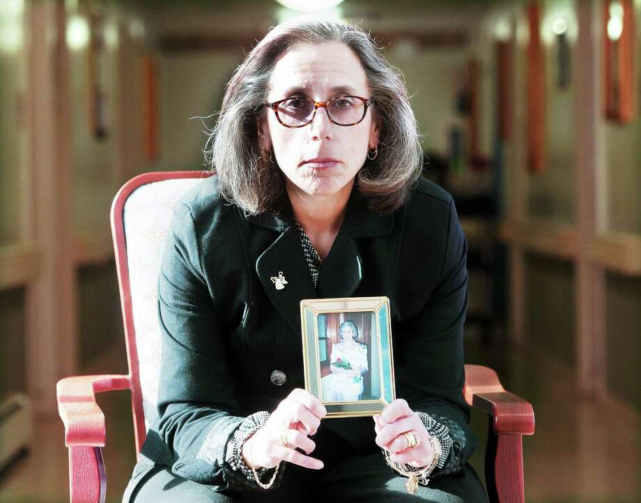 Gina D'Agostino holds a photo of her mother, Jeannette Piscitelli, who died in May. Piscitelli suffered from depression at the end of her life. She is shown at the Guilford Apple Rehab, where Piscitelli lived at the end of her life.  pcasolino@NewHavenRegister Photo: (Peter Casolino - New Haven Register)