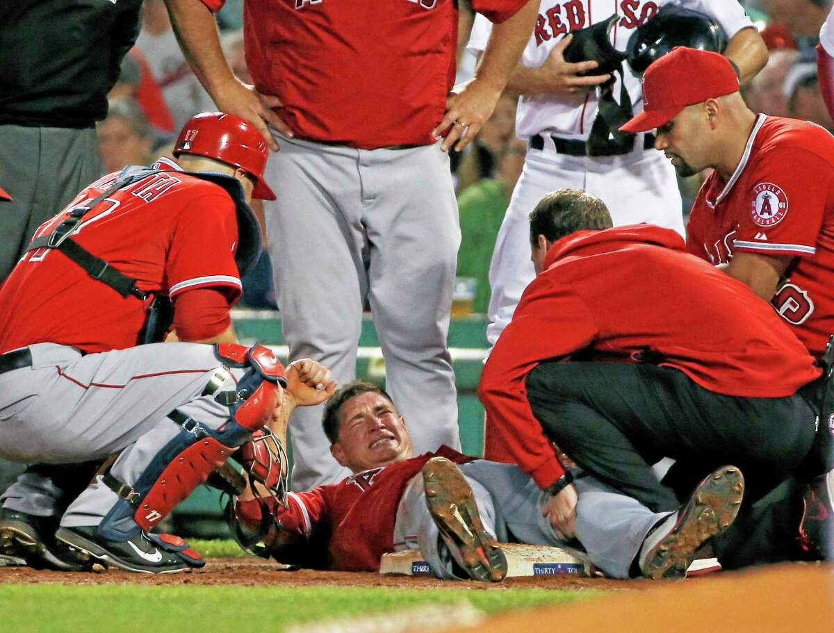 Los Angeles Angels starter Garrett Richards is attended to on the field after injuring his knee during the second inning of Wednesday's game against the Red Sox at Fenway Park in Boston.