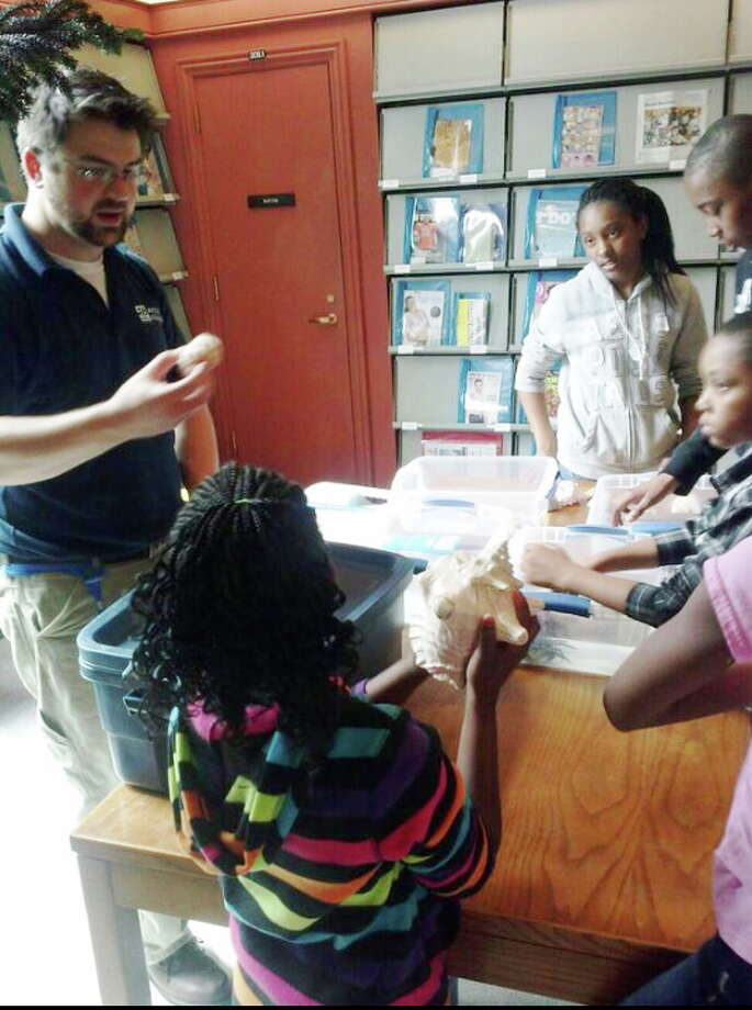 Stephen Marquis, part-time instructor at Mystic Aquarium, speaks to children about sea life at a recent event at the New Haven Free Public Library. Photo: Aaron Berkowitz