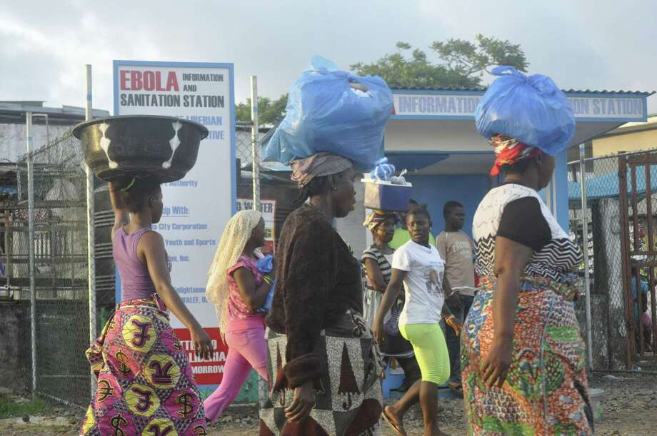 Women walk past a sign warning people of the deadly Ebola virus in Monrovia, Liberia.  (AP Photo/ Abbas Dulleh) Photo: AP / AP