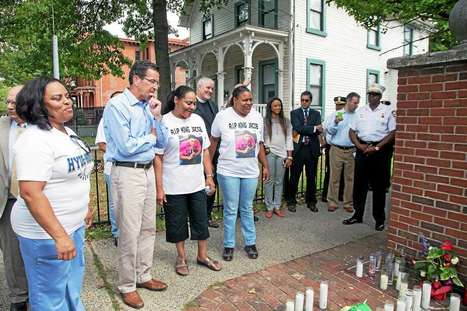 Governor Dan Malloy observes a memorial set-up for homicide victim Jacob Craggett, 15, who was shot earlier this month in the Hill. His mother Lisa Craggett (right of Malloy) talks about a scholarship fund she set up in her son's honor. Photo: (Rich Scinto — New Haven Register)