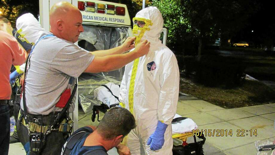 New Haven firefighters help emergency technicians from AMR prepare and suit up to transport a patient to Yale-New Haven Hospital Wednesday night. Photo: CONTRIBUTED PHOTO