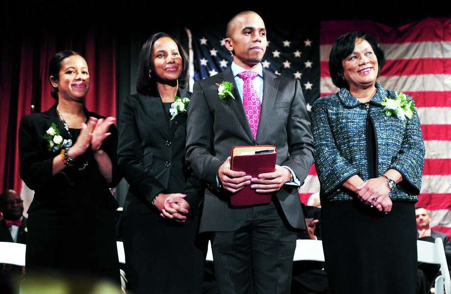 New Haven Mayor Toni N. Harp, right, listens to Lubbie Harper Jr. speak before swearing her in at inauguration ceremonies at Hill Regional Career High School in New Haven Wednesday. Harp's children, from left, Djana Harp, Jamil Harp and Matthew Harp, joined her on stage. Photo: Arnold Gold — New Haven Register