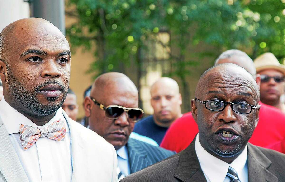 Former city firefighter Aaron Brantley, left, stands with the Rev. William Mathis during a press conference announcing Brantley's appeal in his criminal bribery case.
