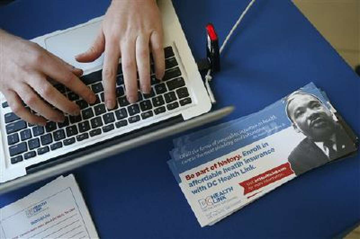David Bransfield, a state outreach coordinator for Young Invincibles, a group which supports President Barack Obama's health care law, works on his computer at a table set up to sign people up for health care at the University of the District of Columbia in Washington, Thursday, Jan. 30, 2014. An army of workers and volunteers has fanned out around the country trying to enroll young and healthy people in health insurance now available through Obama?s signature law. (AP Photo/Charles Dharapak)