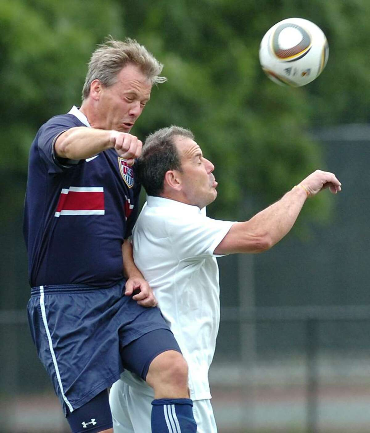 Paul Korngiebel, left, playing for team USA heads the ball over Martin Waters, playing for the English team, during a pick-up game of soccer between Yanks and Brits at Greenwich High School, June 12, 2010. Both men are Greenwich residents.
