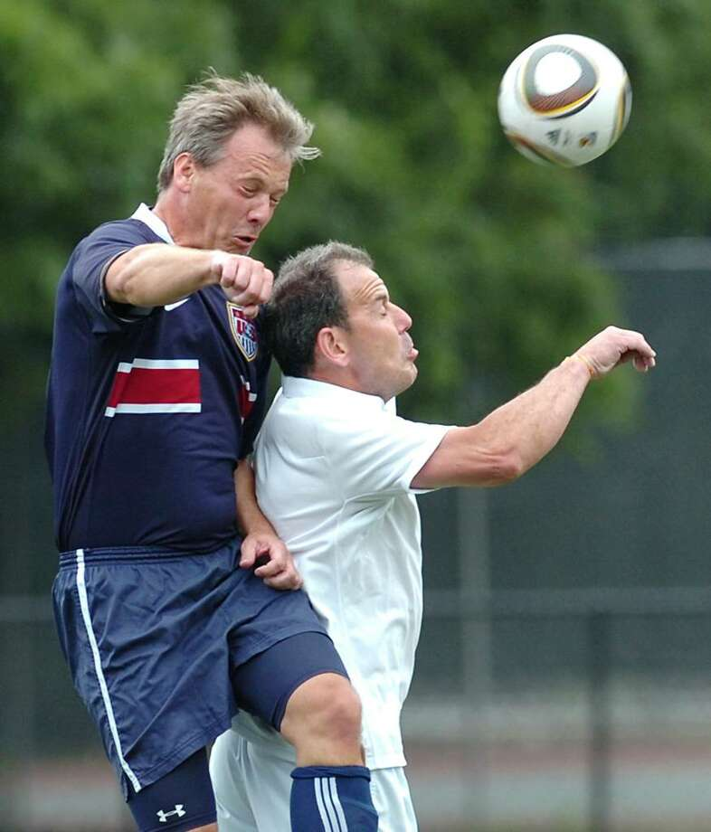 Paul Korngiebel, left, playing for team USA heads the ball over Martin Waters, playing for the English team, during a pick-up game of soccer between Yanks and Brits at Greenwich High School, June 12, 2010.  Both men are Greenwich residents. Photo: Bob Luckey / Greenwich Time