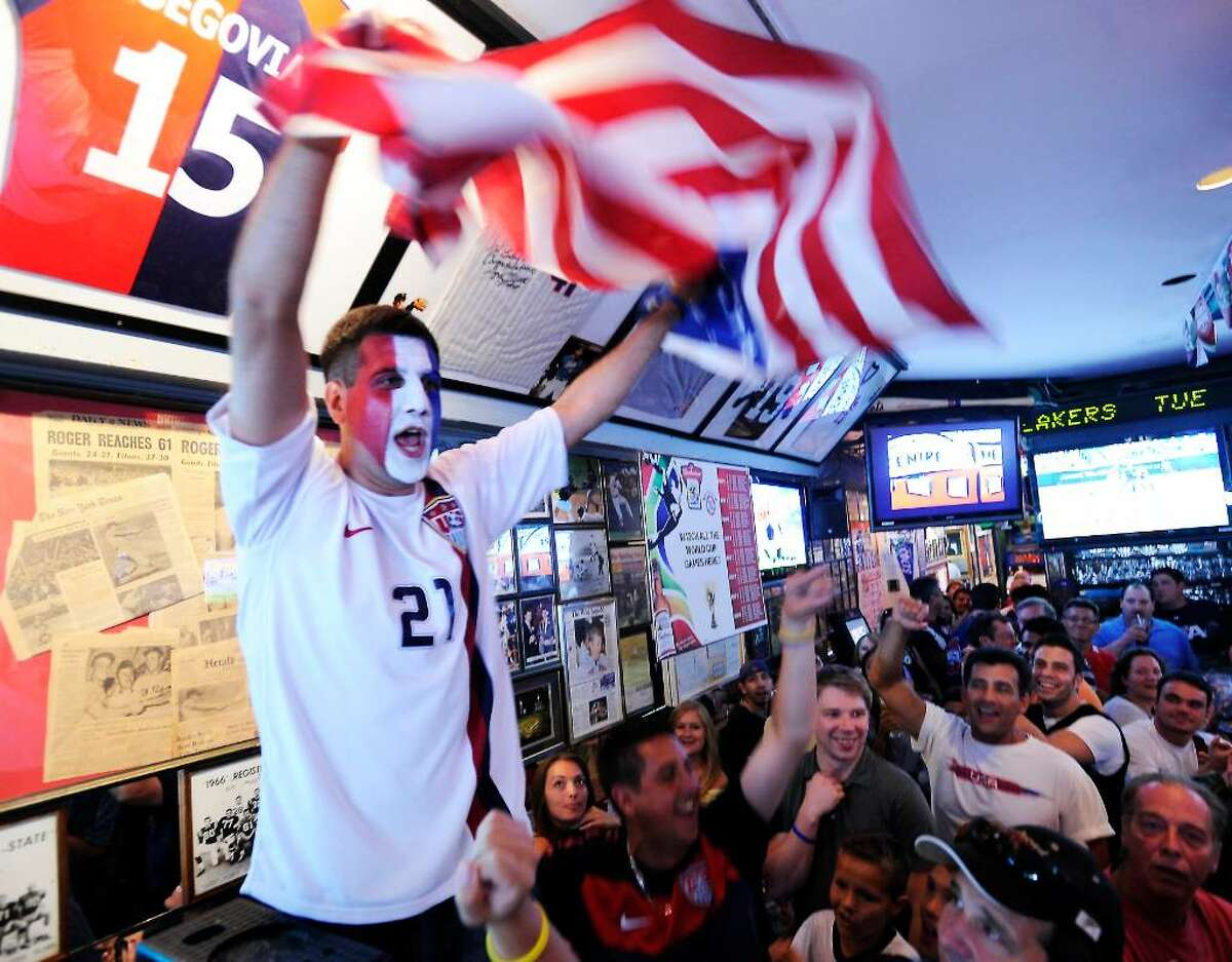Sean Segovia unveils his brother Keith's professional jersey from Poland (Piast Gliwice) during the halftime of the USA v England world cup game at Bobby Valentine's Sports Gallery Cafe in Stamford, Conn. on Saturday June 12, 2010. Keith Segovia, the former Stamford High School soccer star who went on to win a national championship at Southern Connecticut State University and play professionally in Europe, lost his long battle with cancer in January.