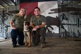 """USMC veteran Juan Solis, right, of Houston, kneels for a photo with his new dog """"Tex"""", a 16 month old Belgian Malinois, and Amy Noyes, of Riverside, CA., and a trainer for Rebuilding Warriors, after """"Tex"""" was presented to Solis at a ceremony held at Tin Roof BBQ in Humble on July 22, 2017. Rebuilding Warriors is a non-profit organization that provides highly trained and socialized Service/Companion Dogs to Veterans diagnosed as Amputees as well as those with PTSD Post Traumatic Stress Disorder) and TBI (Traumatic Brain Injury). (Photo by Jerry Baker/Freelance)"""