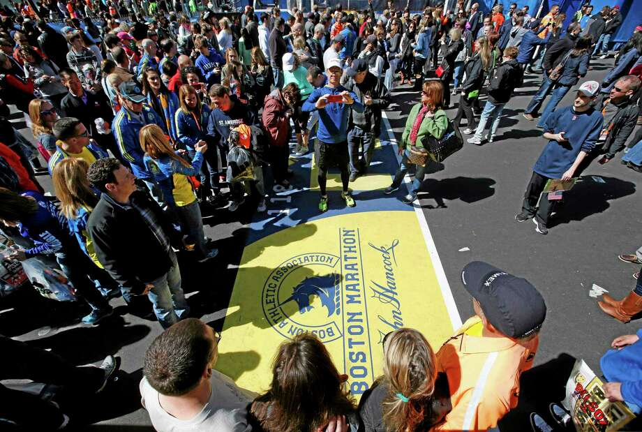 Robert F. Bukaty — The Associated Press   A large crowd gathers to pose for photos at the Boston Marathon finish line, one day before the race in Boston. Photo: AP / AP