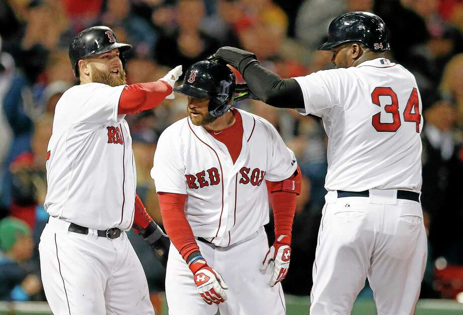 Boston Red Sox's David Ortiz (34) and Mike Napoli, left, celebrate after scoring a on a three-run home run by Jonny Gomes, center, in the sixth inning of a baseball game against the Baltimore Orioles in Boston, Sunday, April 20, 2014. (AP Photo/Michael Dwyer) Photo: AP / AP