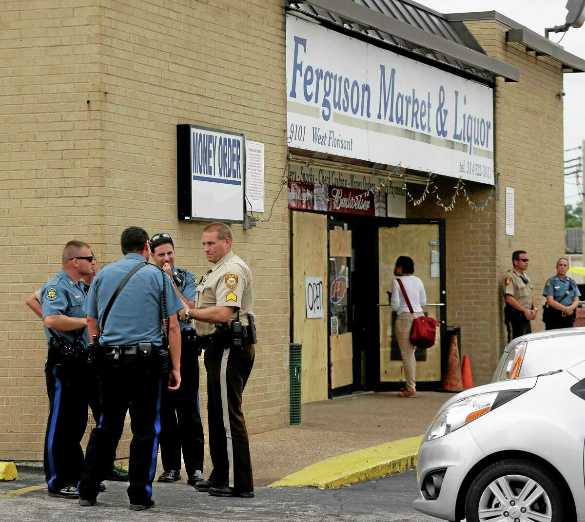 Law enforcement officers stand watch outside a market, Friday, Aug. 15, 2014, in Ferguson, Mo.