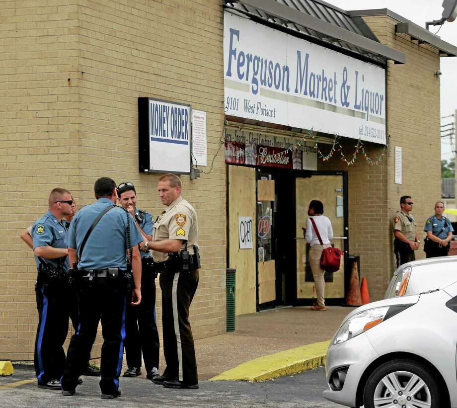 Law enforcement officers stand watch outside a market, Friday, Aug. 15, 2014, in Ferguson, Mo. Photo: (Charlie Riedel — The Associated Press) / AP