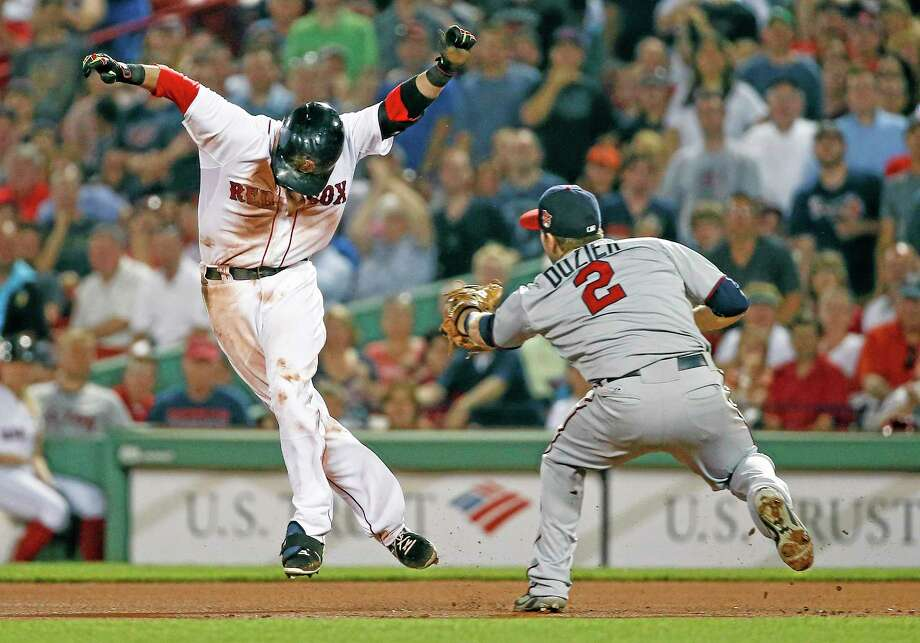 The Red Sox's Dustin Pedroia is tagged out by Minnesota Twins second baseman Brian Dozier (2) after being caught between first and second base after hitting a single in the eighth inning Tuesday. Photo: Elise Amendola  — The Associated Press   / AP