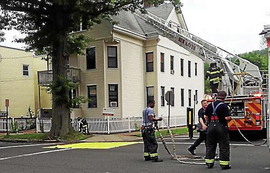 Fire crews extinguished a house fire Tuesday morning at 31 Canner St. in New Haven. Lt. Ben Vargas said the fire started with a light fixture on the second floor and extended to the third floor of the home. Photo: Kristin Stoller — New Haven Register