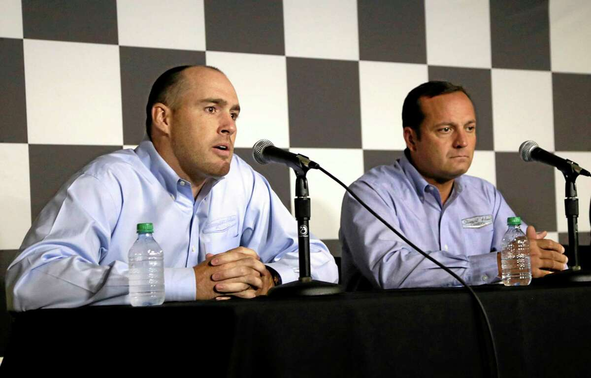 Stewart-Haas Racing executive vice president Brett Frood, left, speaks during a news conference as crew chief Greg Zipadelli looks on Friday at Michigan International Speedway in Brooklyn, Mich.