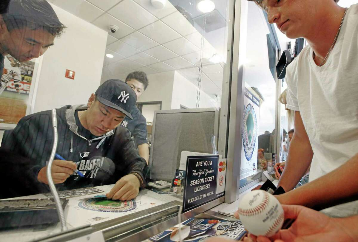 New York Yankees starting pitcher Masahiro Tanaka, who is on the disabled list with a sore elbow, sells advance tickets to fans with the help of an interpreter before the Aug. 6 game at Yankee Stadium in New York.