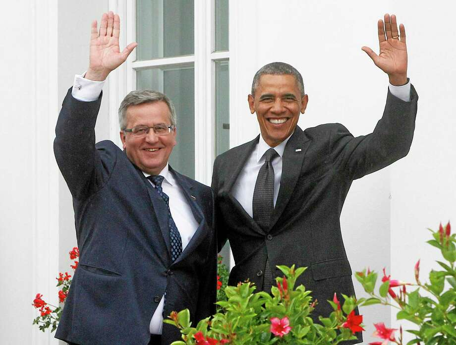 U.S. President Barack Obama,right, and Poland's President Bronislaw Komorowski ,left, wave wave at Belveder residence in Warsaw, Poland, on Tuesday June 3, 2014.Obama came to Poland to meet regional leaders and attend ceremonies marking 25 years of Poland's democracy. (AP Photo/Czarek Sokolowski) Photo: AP / AP