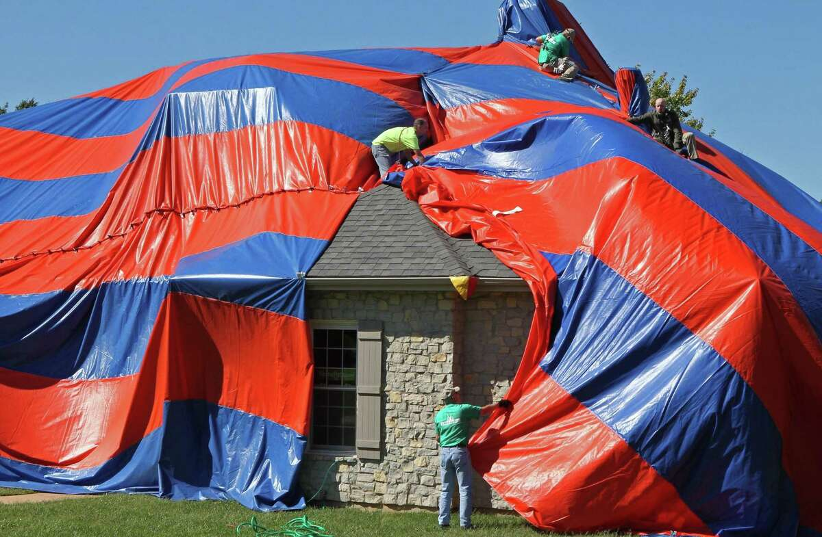 In this photo taken on Oct. 5, workers from McCarthy Pest Control finish covering a house in Dardenne Prairie, Mo. with a tarp in preparation for fumigating the home to get rid of brown recluse spiders. (AP Photo/St. Louis Post-Dispatch, J.B. Forbes)