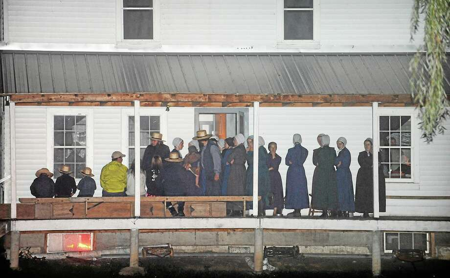 Supporters gather on the porch of a house at the intersection of Route 812 and Mt. Alone Road in Heuvelton, NY on Thursday, Aug. 14, 2014 after Fannie Miller, 12, and her sister Delila Miller, 6, were returned home safely after being abducted Wednesday night at a farm stand near their home. (AP Photo/The Watertown Daily Times, Jason Hunter) Photo: AP / The Watertown Daily Times