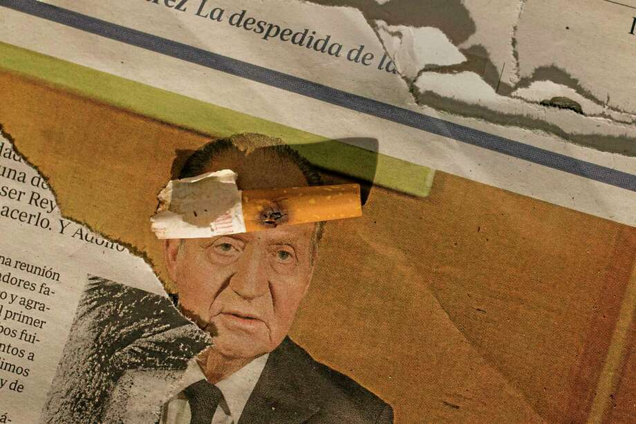 """A burned cigarette lays on a newspaper with the image of Spain's King Juan Carlos, inside a house, property of Barclays bank, occupied by the Ovid family from Romania, during their eviction in Madrid, Spain, Tuesday, June 17, 2014. King Juan Carlos said he was stepping aside so that fresh royal blood could rally the nation. 46-year-old Prince Felipe will be proclaimed king on June 19. Juan Carlos became king in 1975, two days after the death of longtime dictator Gen. Francisco Franco. He won massive support by staring down a 1981 coup attempt. Newspaper's partly seen text """"reads: """"the good bye÷to be king."""" (AP Photo/Andres Kudacki) Photo: AP / AP"""