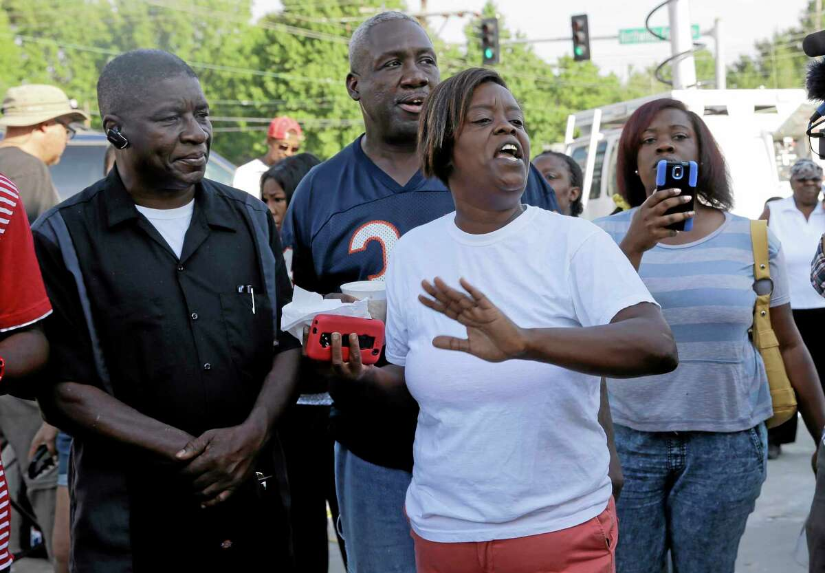 People react after Ferguson Police Chief Thomas Jackson releases the name of the the officer accused of fatally shooting Michael Brown, an unarmed black teenager, Friday, Aug. 15, 2014, in Ferguson, Mo. The officer's name is Darren Wilson, a six-year veteran of the force.