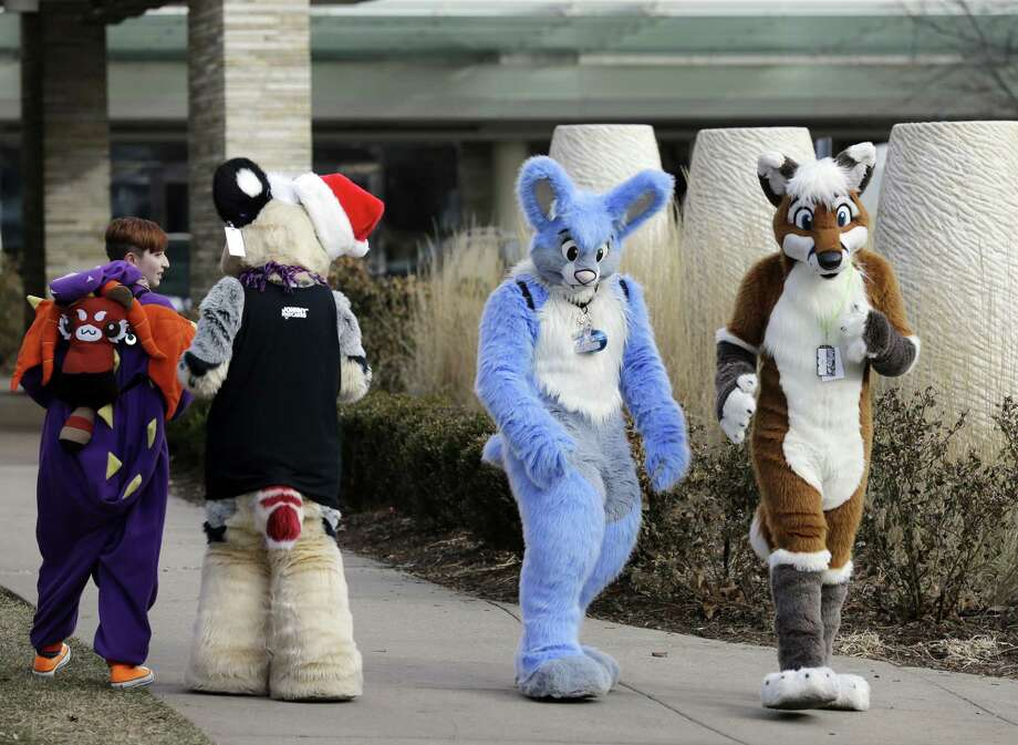 Frederic Cesbron, right and Maxim Durand, walk on the street outside the Hyatt Regency O'Hare hotel on Sunday, Dec. 7, 2014, in Rosemont, Ill. Thousands of people were evacuated after a chlorine gas leak at the hotel hosting the 2014 Midwest FurFest convention, where attendees dress as animals to celebrate art, literature and performance, in suburban Rosemont early Sunday morning. Investigators believe the leak at the hotel in Rosemont was caused intentionally and are treating it as a criminal matter. (AP Photo/Nam Y. Huh) Photo: AP / AP